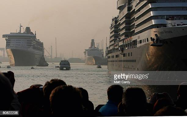 People watch from the quay side as the cruise liner Queen Mary 2 passes the Queen Elizabeth 2 and the Queen Victoria on April 22 2008 in Southampton...