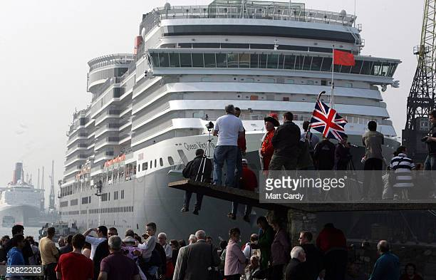 People watch from the quay side as they wait for cruise liner Queen Mary 2 to passe the Queen Elizabeth 2 and the Queen Victoria on April 22 2008 in...