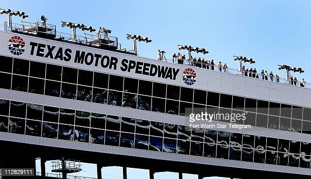 People watch from the roof of the grandstands between turns one and two before the NCWTS 7Eleven Qualifying at the Texas Motor Speedway Thursday...