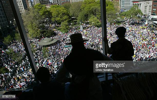 People watch from the top floor windows of a department store a rally of thousands against proposed crackdowns on illegal immigrants in Union Square...