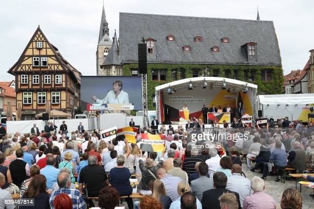 People watch German Chancellor and Christian Democrat Angela Merkel speak on Markt square during an election campaign stop on August 26 2017 in...