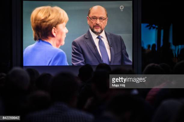 People watch German Chancellor and Christian Democrat Angela Merkel debate with her main opponent Social Democrat and chancellor candidate Martin...