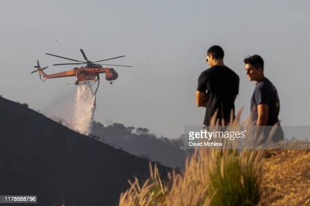 People watch helicopters make water drops on the Getty Fire on October 28 2019 in Los Angeles California Reported at 130 am the fire burned several...
