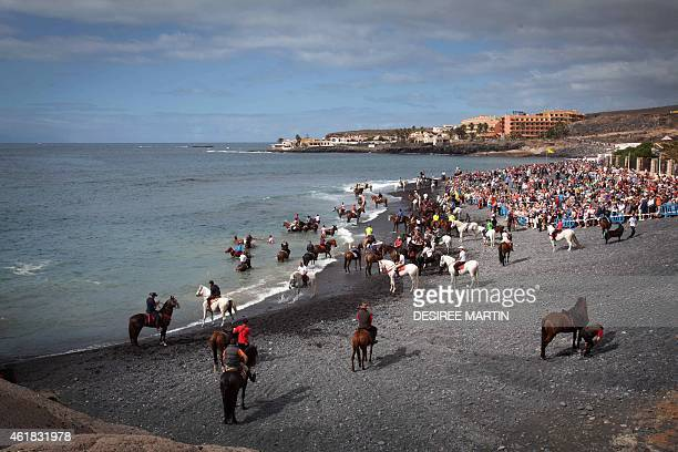 People watch horses ridden into the surf at la Enramada beach along the southern Adeje coastline on the Canary island of Tenerife on January 20 2015...