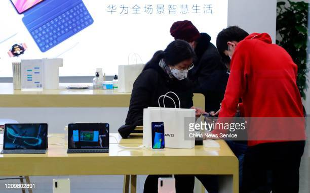 People watch Huawei smartphones at a store on March 1 2020 in Shanghai China Shanghai is seeing acceleration in work resumption amid the novel...