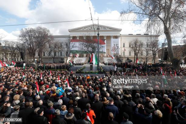People watch Hungarian Prime Minister Viktor Orban deliver a speech in front of the National Museum during Hungary's National Day celebrations on...
