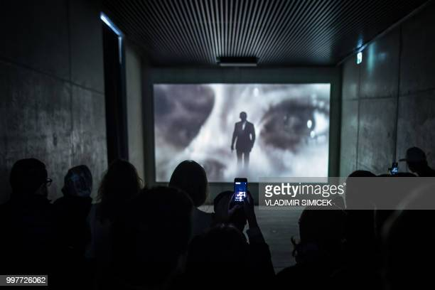 People watch images on a screen during a visit at the James Bond cinematic installation named '007 ELEMENTS' on July 11 2018 at the top of the...