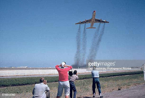 People watch jets takeoff from the end of a runway San Francisco 1956