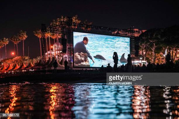 TOPSHOT People watch late on May 11 2018 the 30th anniversary screening of the film Le Grand Bleu at the Cinema de la Plage on the sidelines of the...