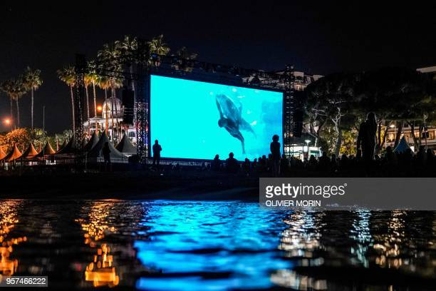 TOPSHOT People watch late on May 11 2018 the 30th anniversary screening of the film 'Le Grand Bleu' at the Cinema de la Plage on the sidelines of the...