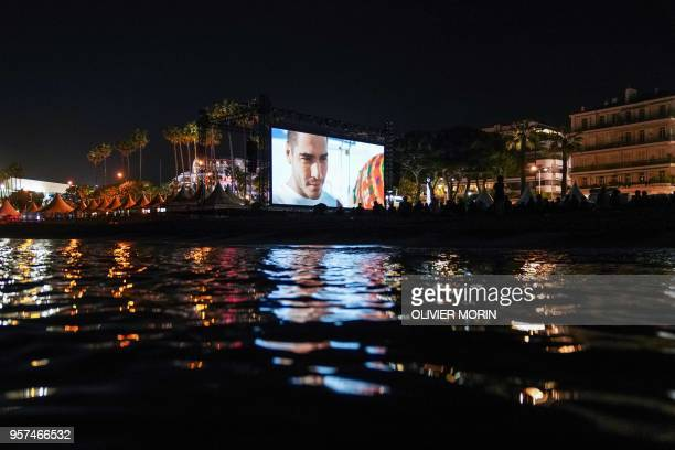 People watch late on May 11 2018 the 30th anniversary screening of the film 'Le Grand Bleu' at the Cinema de la Plage on the sidelines of the 71st...
