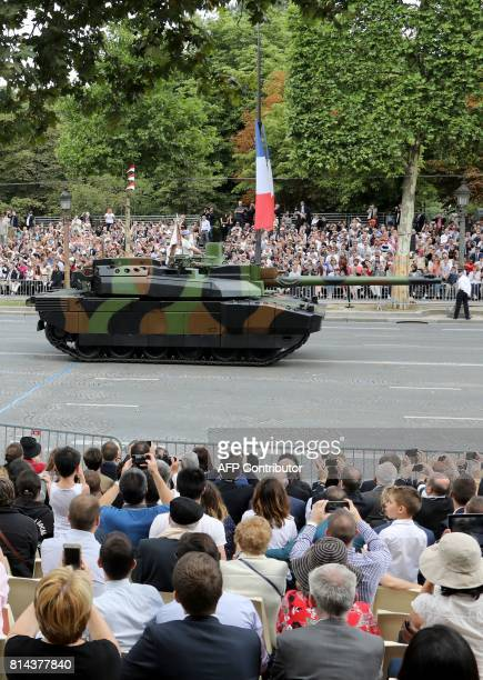 People watch Leclerc main battle tanks during the military parade during Bastille Day celebrations on Champs Elysees avenue in Paris on July 14,...