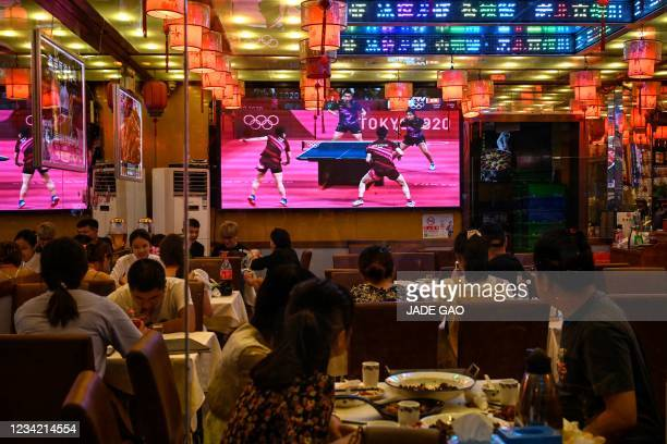 People watch live coverage of the mixed doubles table tennis final match between China and Japan during the Tokyo 2020 Olympic Games at a restaurant...