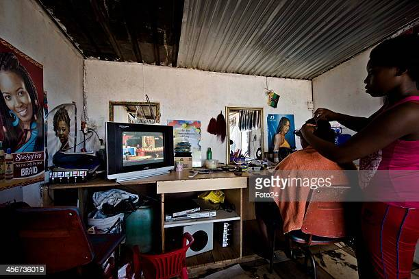 People watch Madiba's State Funeral at a salon on December 15 2013 in Tokoza South Africa Nelson Mandela passed away on the evening of December 5...