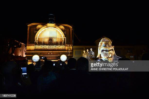 People watch movies projected on the facade of the world's oldest cinema theater L'Eden during its official reopening on October 9 2013 in La Ciotat...
