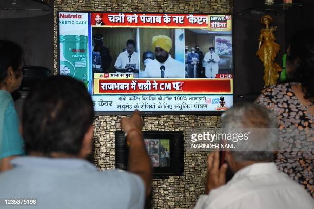 People watch newly appointed Punjab Chief Minister Charanjit Singh Channi oath-taking ceremony on television in Amritsar on September 20, 2021.