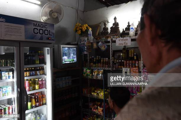 People watch news on television at a store in Chiang Rai broadcasting the rescue operations of children's football team trapped in Tham Luang cave on...