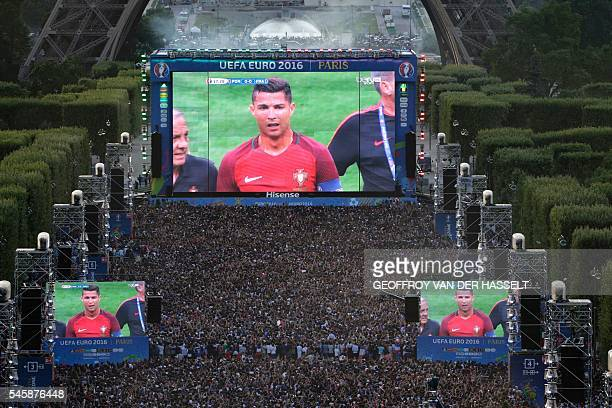 People watch on a giant screen the Euro 2016 football tournament final match between Portugal and France on July 10 2016 at the fan zone of the...