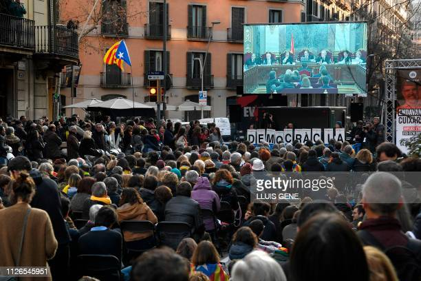 People watch on a screen today's session of the trial of former Catalan separatist leaders held in Madrid during a strike day in Barcelona to protest...