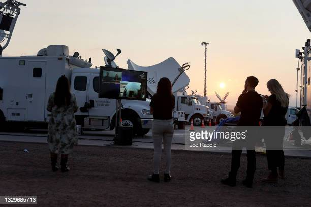 People watch on a television screen as the New Shepard Blue Origin rocket sits on the launch pad before Jeff Bezos along with his brother Mark Bezos,...