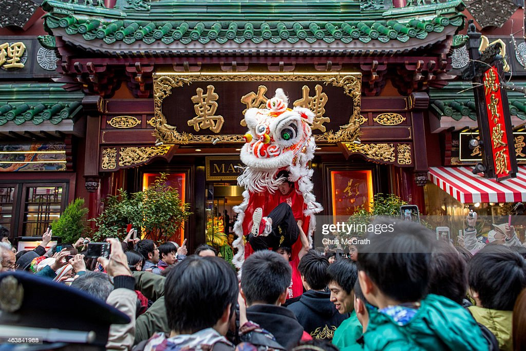 people watch on as a a lion dance is performed to celebrate the chinese new year outside - Chinese New Year 1988