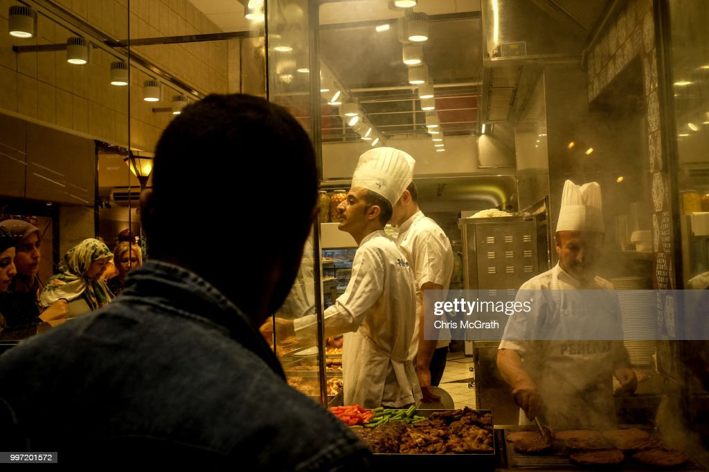 People watch on as food is prepared in the window of a restaurant on July 12, 2018 in Istanbul Turkey. Following Turkey's President Recep Tayyip Erdogan's re-election victory and the appointment of his son-in-law Berat Albayrak to lead the Treasury and Finance Ministry fears are growing that Turkey's economy is heading into crisis . The Turkish Lira, has plunged by approximately one-fifth this year raising prices for businesses and households.