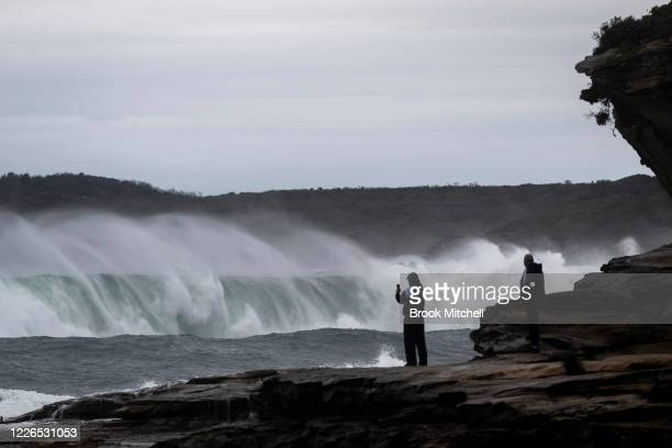 People watch on as huge waves break inside Botany Bay at La Perouse on May 23 2020 in Sydney Australia Winter weather including rain and strong winds...