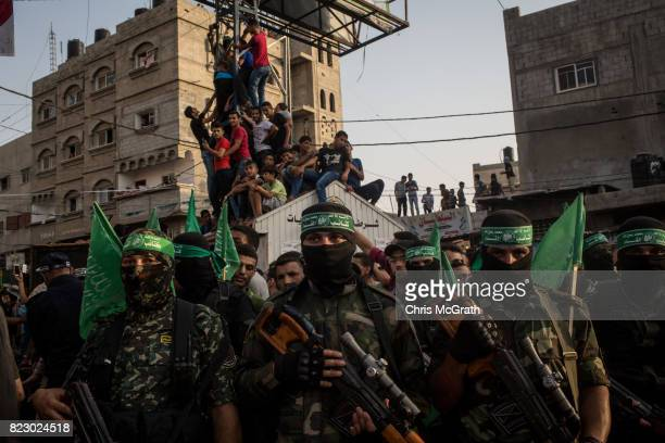 People watch on as Palestinian Hamas militants take part in a military show in the Bani Suheila district on July 20 2017 in Gaza City Gaza For the...