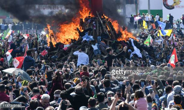 People watch on as the Nowruz fire is lit during Nowruz festivities on March 21 2019 in Diyarbakir Turkey Nowruz marks the Persian New Year as well...