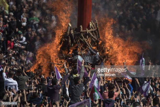 People watch on as the Nowruz fire is lit during Nowruz festivities on March 21 2018 in Diyarbakor Turkey Nowruz meaning new day is widely celebrated...