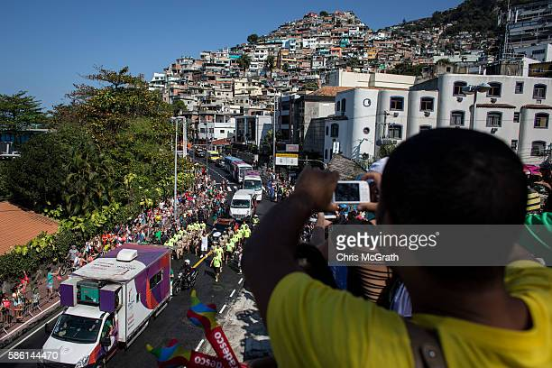 People watch on from the Vidigal 'favela' community as the Olympic torch passes by during the Olympic torch relay on August 5 2016 in Rio de Janeiro...