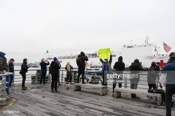 People watch on Pier 84 while the USNS Comfort hospital ship travels up the Hudson River as it heads to Pier 90 during the Coronavirus pandemic on...
