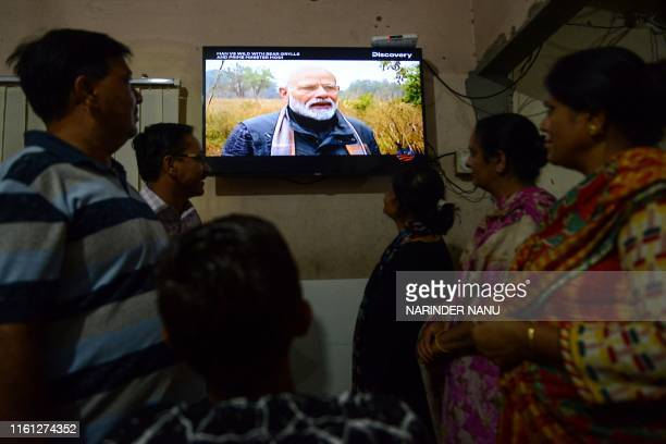 People watch on television the 'Man VS Wild' hosted by survival expert Bear Grylls going on a mission with Indian Prime Minister Narendra Modi in...
