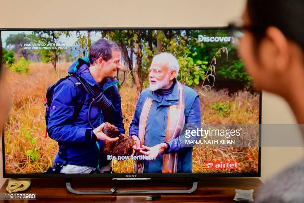 People watch on television the special edition of 'Man Vs Wild' series hosted by survival expert Bear Grylls going on a mission with Indian Prime...