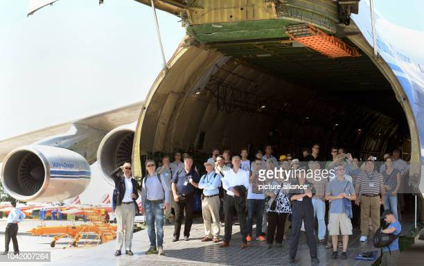 People watch performances in the shade of an Antonov An124 for demonstration purposes at the ILA Berlin Air Show 2014 in Selchow Germany 21 May 2014...