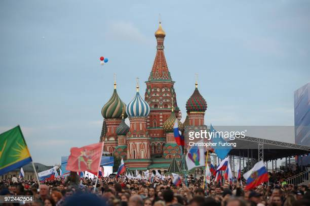 People watch performers on stage in Red Square during a concert to celebrate 'Russia Day' ahead of the 2018 World Cup on June 12 2018 in Moscow...