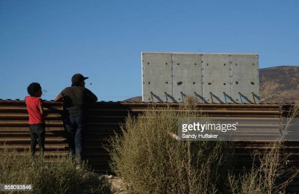 People watch prototype sections of a border wall between Mexico and the United States under construction on October 5 2017 in Tijuana Mexico...