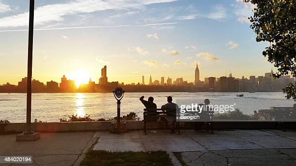 people watch scenic sunset over new york city skyline - williamsburg new york city stock pictures, royalty-free photos & images