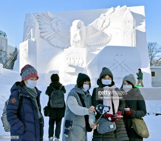 People watch snow statues as the Sapporo Snow Festival begins at the Odori Park on February 4, 2020 in Sapporo, Hokkaido, Japan.