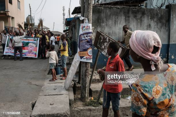 People watch supporters of Nigeria's incumbent President's party the All Progressives Congress on a street in Port Harcourt, the opposition...
