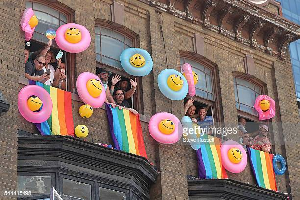 TORONTO ON JULY 3 People watch the 2016 Toronto Pride parade along Yonge Street in Toronto July 3 2016
