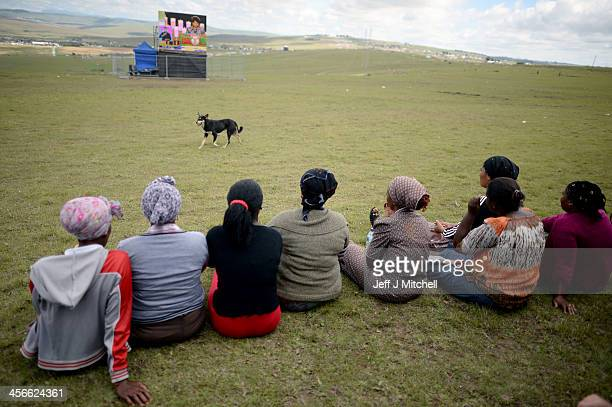 People watch the big screens at the site where former South African President Nelson Mandela will be buried on his family's property in his childhood...