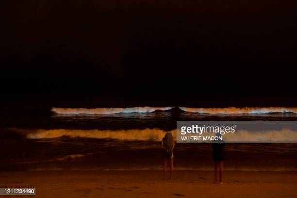 People watch the bioluminescent waves crash on the sand shining with a blue glow on April 28 in Manhattan Beach California Bioluminescence is a...