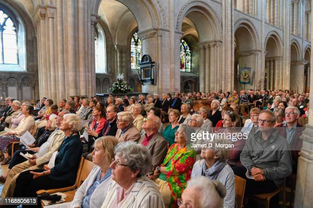 People watch The Bishop of Lynn, the Rt Revd Jonathan Meyrick as he gives his sermon on the slide of the helter skelter inside the nave of the...
