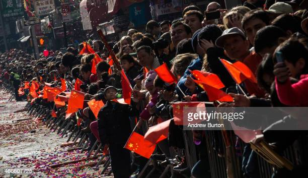 People watch the Chinese New Year Parade on February 2 2014 in the Chinatown neighborhood of New York City The parade which is in it's 15th year in...