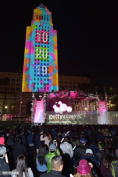 People watch the countdown clock projected onto City Hall's facade as they gathered for New Year celebrations at the Grand Park in Los Angeles CA USA...
