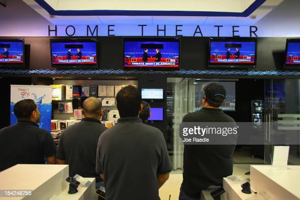 People watch the debate between US President Barack Obama and Republican presidential candidate and former Massachusetts Governor Mitt Romney as they...