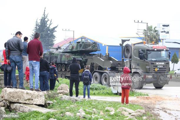People watch the deployment of tanks by Turkish military trucks to reinforce the border units in Antakya district of Hatay Turkey on January 18 2018