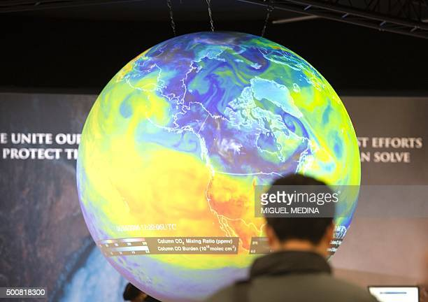 People watch the Earth globe at the COP21 the United Nations conference on climate change in Le Bourget on December 10 2015 Weary ministers tasked...