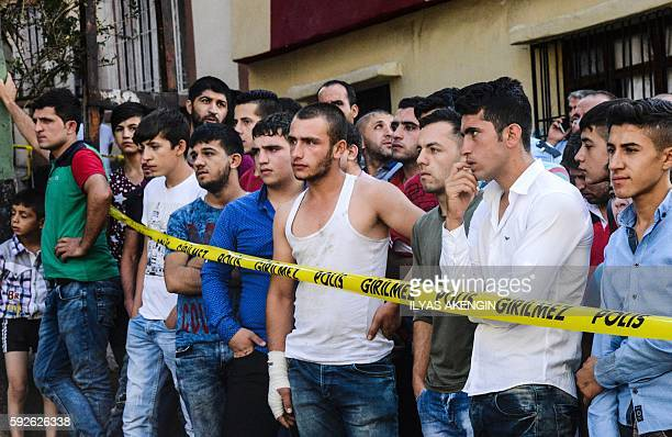 People watch the explosion scene following a late night attack on a wedding party that left at least 30 dead in Gaziantep in southeastern Turkey near...